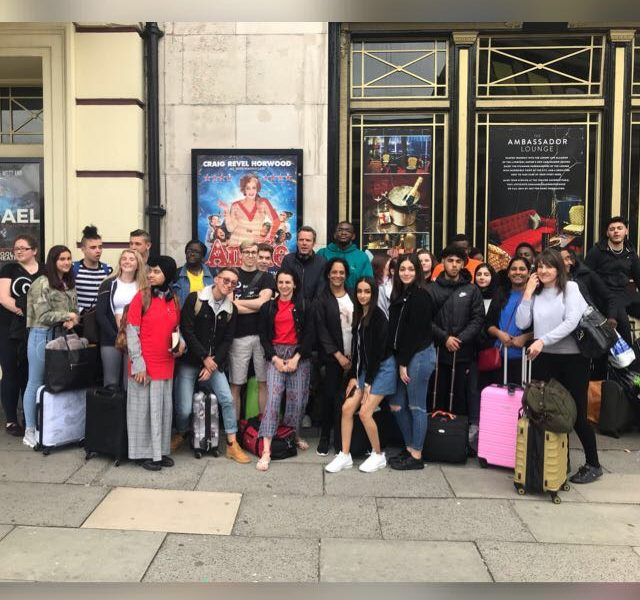 19 learners from schools pose for photograph in front of theatre