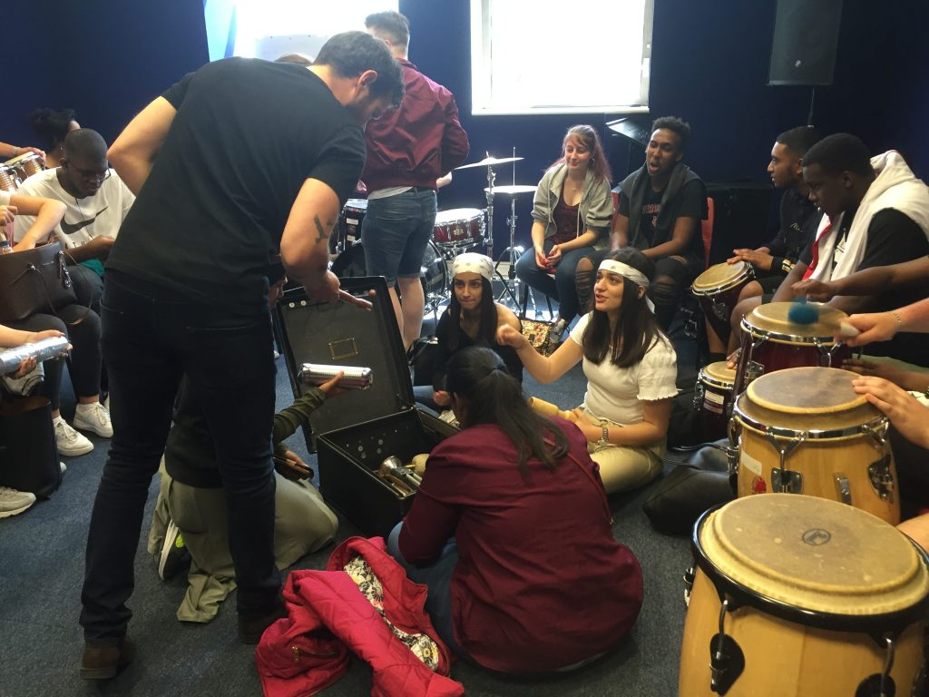 Students gathering around box of music instruments, learners also play bongos in small music room